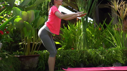 Woman doing squats, exercising in garden