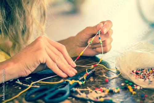 Leinwandbild Motiv Making bracelet of colorful beads