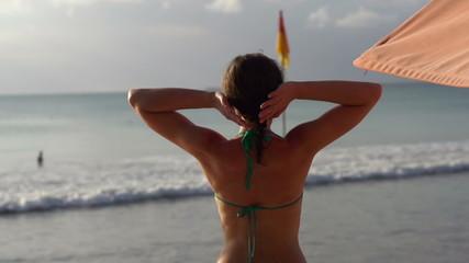 Sexy woman in bikini streatching by the sea