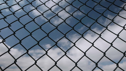 Fast moving clouds behind a chain link fence.