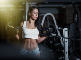 Woman bodybuilder training with dumbbell. © fotoatelie