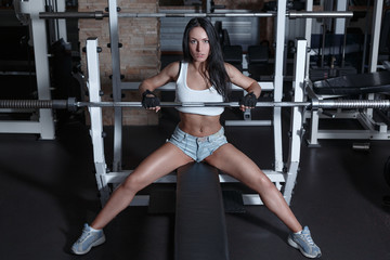 Young beautiful woman is training in the gym with a barbell