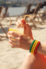 Fresh lemonade in the women's hand on the beach