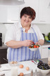 Overweight and smiling woman making breakfast.