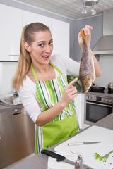 Frau in der Küche hält frischen Fisch: Barsch