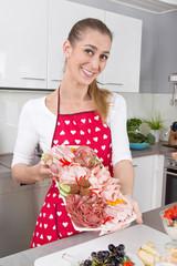 Frau in der Küche präsentiert eine Wurstplatte