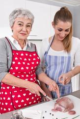 Mutter und Tochter in der Küche bereiten Schweinebraten zu.