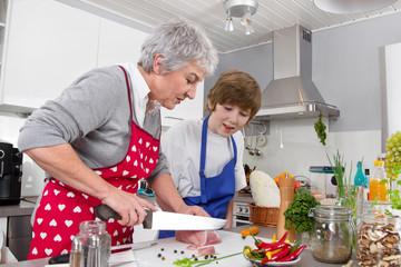 Großmutter kocht mit ihrem Enkel Fleisch