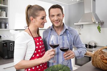 Junges verliebtes Paar trinkt Rotwein: erste gemeinsame Wohnung
