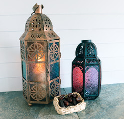 Glass and bronze coloured metal lanterns a basket of dates