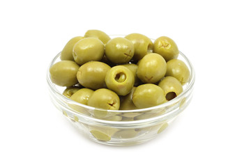 green stuffed olives in a glass on white background
