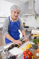 Ältere Frau bereitet Fisch zu: Barsch und Hecht
