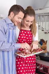 Junges Paar in der Küche isst Wurst