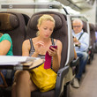 Lady traveling by train using smartphone.