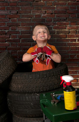Cute and funny little mechanic with a tire