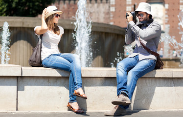 Young couple of turists taking picture in the city