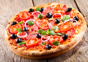pizza with ham, olives and vegetables
