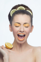 Young woman with oranges and makeup