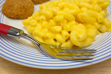 Chicken nuggets with macaroni on plate with fork