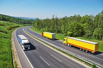The highway between forests with three oncoming trucks