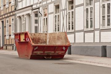 Ein leerer roter Bauschuttcontainer vor einem Fachwerkhaus