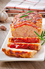 Homemade ground meatloaf with ketchup and rosemary