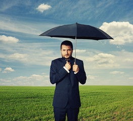 man under black umbrella at outdoor