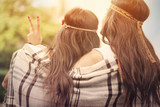 Boho female friends with blanket looking on sunset poster