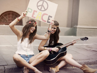 Hippie beautiful friends playing guitar in the city