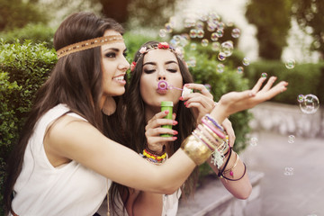 Hippie two beautiful girls blowing bubbles