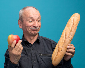 Doubting man with apple and baguette