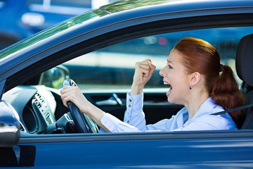 Angry young screaming female car driver, side window view