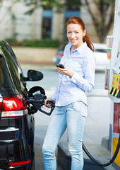 Young happy woman at gas station, filling up her car tank