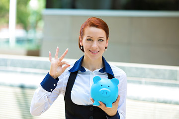 Happy woman, corporate employee holding piggy bank giving ok