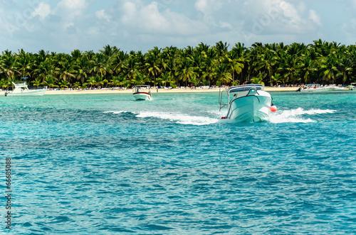 Papiers peints Amérique Centrale Motorboat on the azure sea on a background of exotic beach