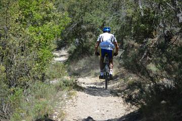 ciclista  circulando por un camino en la montaña