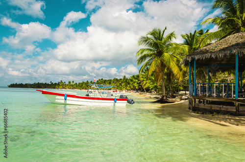 Papiers peints Amérique Centrale Boat moored off the coast of the island full of palm trees