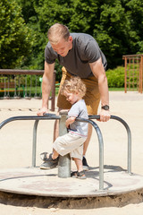 Dad and son playing on merry-go-round