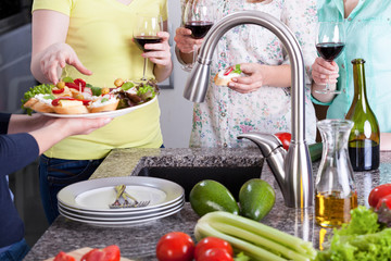 Women with sandwiches and glasses of wine standing in kitchen