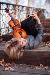 Mature woman playing viola and lying on the wooden bridge
