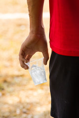 hand of athlete holding glass of iced water against strong sunli
