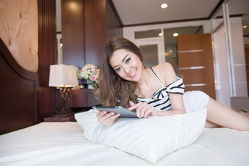 Young beautiful woman playing tablet