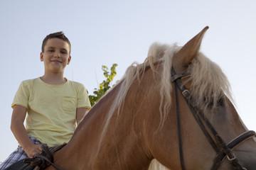 Niño con camiseta amarilla montado a caballo
