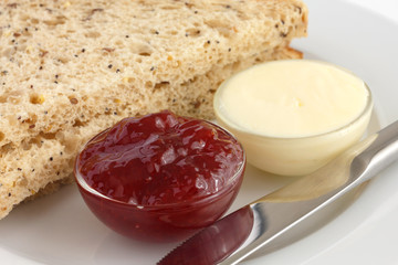 Two slices of multigrain bread with jam and butter in dishes