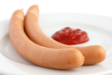 Two frankfurter sausages on a plate with ketchup