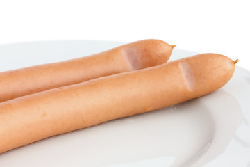 Two cooked frankfurter sausages on a plate with white background