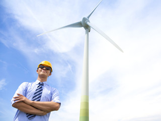professional young engineer standing with wind generator