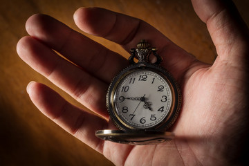 Pocket watch in human hand.