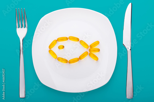 fish oil soft gels lying on a plate - 66692457
