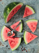 Watermelon sliced in triangle pieces on an old metal board